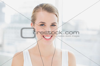 Head shot of cheerful sporty woman listening to music