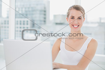 Cheerful blonde using her laptop