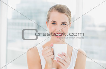 Smiling blond woman holding cup of coffee