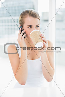 Smiling blond woman on the phone drinking coffee