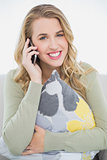 Smiling pretty blonde on the phone sitting on cosy sofa