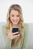 Smiling pretty blonde sending a text sitting on cosy sofa