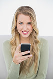 Cheerful pretty blonde sending a text sitting on cosy sofa