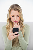 Thinking pretty blonde sending a text sitting on cosy sofa