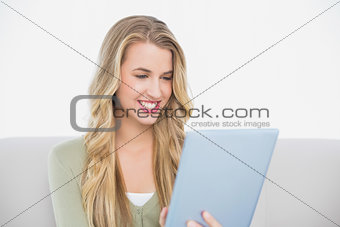 Smiling pretty blonde using her tablet sitting on cosy sofa