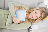 Overhead of pretty blonde holding her tablet lying on cosy sofa