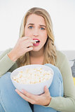 Surprised pretty blonde eating popcorn sitting on cosy sofa
