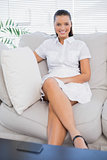 Smiling woman in white dress sitting on sofa