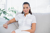 Peaceful woman in white dress sitting on sofa