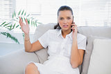 Irritated woman in white dress having a phone call