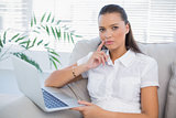 Thoughtful pretty woman using laptop sitting on cosy sofa