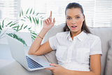 Surprised pretty woman using laptop sitting on cosy sofa