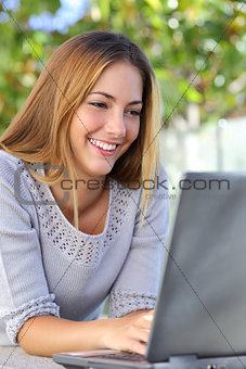 Beautiful woman happy browsing her laptop outdoor