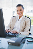 Smiling gorgeous businesswoman working on computer
