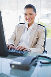Cheerful gorgeous businesswoman working on computer