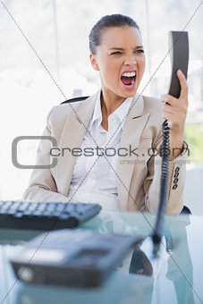 Angry businesswoman screaming at her phone