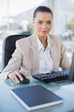 Serious businesswoman working on computer looking at camera