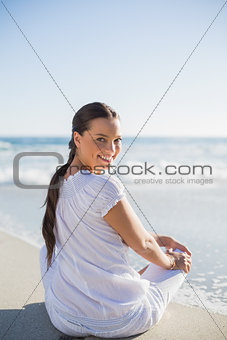 Rear view of smiling woman on the beach looking over shoulder at camera