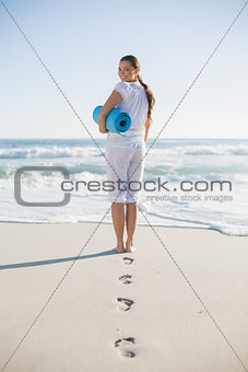 Rear view of gorgeous woman holding exercise mat looking over shoulder at camera
