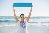 Smiling woman holding exercise mat over her head