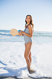 Cheerful woman in one piece swimsuit playing with beach racket