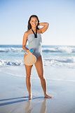 Happy woman in one piece swimsuit posing with beach racket