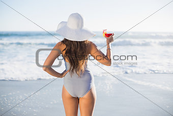 Rear view of gorgeous woman in swimsuit holding cocktail