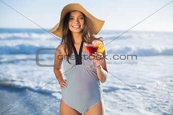 Attractive woman in swimsuit with straw hat holding cocktail