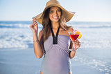 Smiling gorgeous woman in swimsuit wearing straw hat holding cocktail