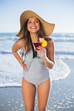 Beautiful woman wearing straw hat holding cocktail