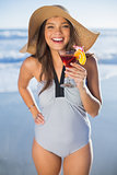Happy woman in swimsuit wearing straw hat holding cocktail