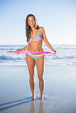 Happy woman in bikini playing with hula hoop