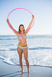 Attractive woman in bikini playing with hula hoop