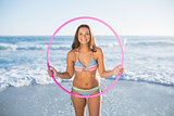Cheerful attractive woman in bikini playing with hula hoop