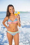 Smiling attractive woman in bikini holding cocktail