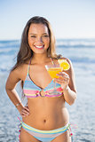 Happy gorgeous woman in bikini holding cocktail