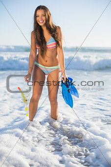 Smiling lovely woman in bikini holding snorkel and fins
