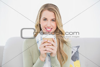 Cheerful cute blonde holding coffee sitting on cosy sofa