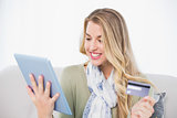 Cheerful pretty blonde using her credit card to buy online