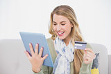 Happy pretty blonde using her credit card to buy online