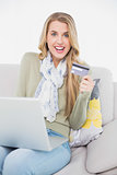 Cheerful cute blonde using her credit card to buy online
