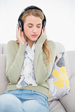 Relaxed cute blonde listening to music sitting on cosy sofa