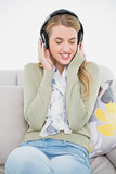 Happy cute blonde listening to music sitting on cosy sofa