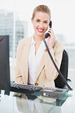 Cheerful pretty businesswoman answering the phone