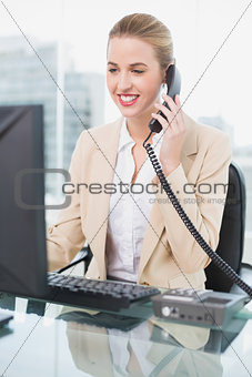 Smiling pretty businesswoman answering the phone