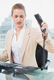Furious pretty businesswoman hanging up the phone