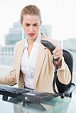 Angry pretty businesswoman hanging up the phone