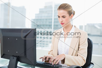 Focused pretty businesswoman working on computer