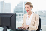 Smiling pretty businesswoman working on computer