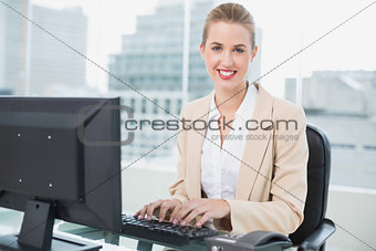Cheerful pretty businesswoman working on computer